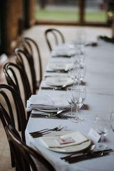 접시, 냅킨, 와인 잔, 포크, 나이프가있는 결혼식 날 장식 된 테이블