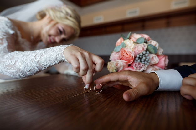 Wedding day. wedding . two wedding rings in the hands of the newlyweds close up. happy bride and groom with their wedding rings