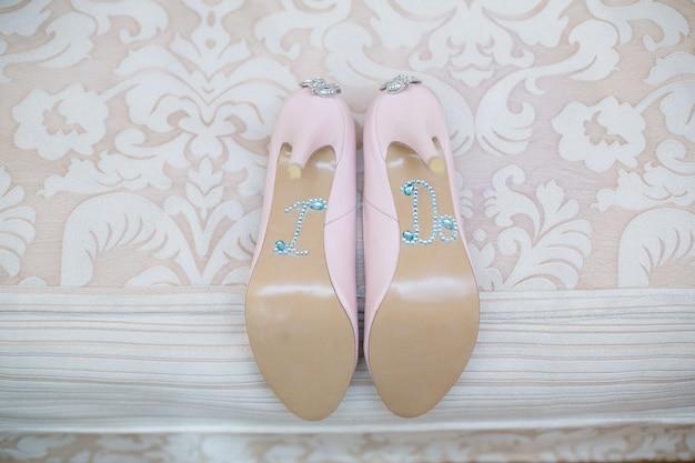 結婚式の日。結婚式の壁。結婚式の詳細とアクセサリー。光沢のあるラインストーンで飾られたピンクのブライダルハイヒールの靴と石をクローズアップ。婦人靴は「私は」という碑文を装飾しました
