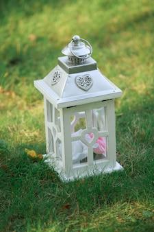 Свадебный декор и флористика. белый деревянный фонарь на зеленой сочной траве крупным планом. белая деревянная лампа. праздничное освещение для залов. праздничное оформление свадьбы или дня рождения на природе