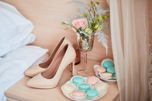 Wedding decor. beige bride's shoes, bouquet and plate with macaroons stand on the table