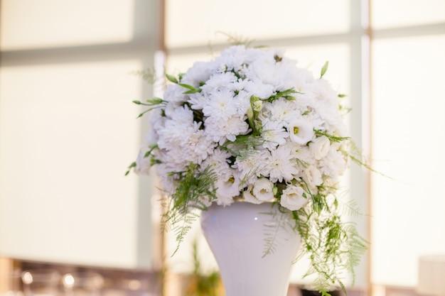 Wedding decor, bouquet of white flowers on gold background in restaurant