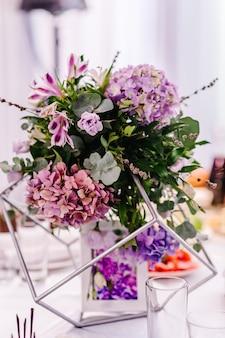 Свадебный декор. праздничный стол в банкетном зале украшен композицией из фиолетовых, пурпурных, розовых цветов и зелени.