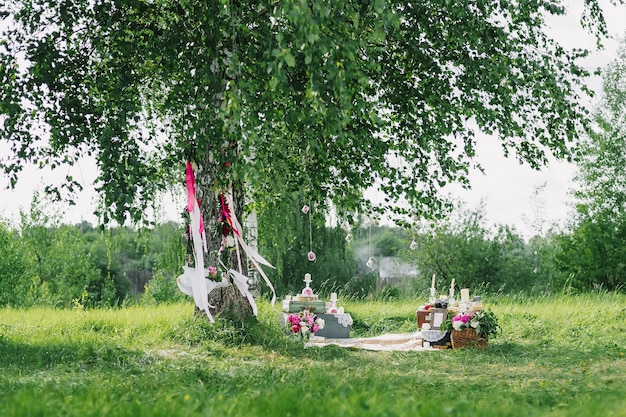 Wedding decor from the flowers and decorations with a swing under the trees outdoors in summer