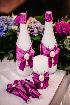 크리스털, 레이스, 꽃이 있는 고급스러운 핑크 스타일의 웨딩 장식. 가족 난로를 위한 웨딩 양초, 테이블에 샴페인 병. 세부. 웨딩 액세서리. 준비 중.