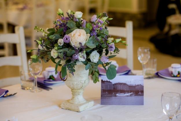 紫の色合いの結婚式の装飾。アンティークの花瓶に新鮮な白いバラと紫色の花の美しいフラワーアレンジメントを備えた美しく装飾されたホリデーテーブル。結婚披露宴、パーティー、お祭り