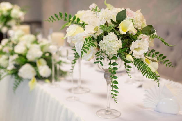 Wedding decor in the interior, white flowers on the table, serving the table with crystal glasses.