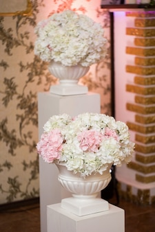 거대한 흰색 꽃병에 흰색과 분홍색 꽃의 웨딩 장식