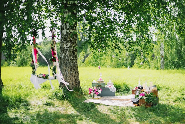 Wedding decor outdoors flowers and a swing in summer sunny day