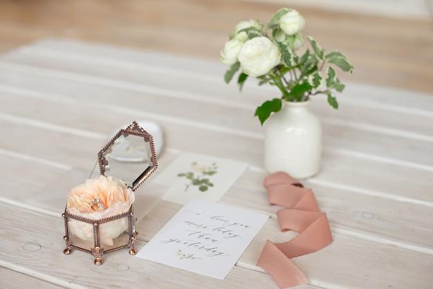 結婚式の装飾ヴィンテージガラス正方形の棺のスタンドと牡丹ローズと結婚指輪の招待状。
