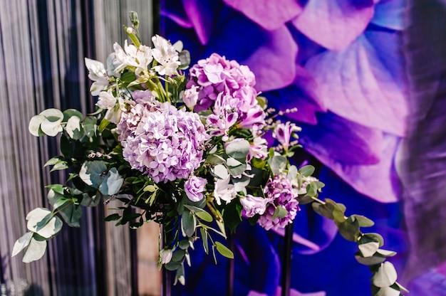 Свадебный декор. стена банкетного зала оформлена композицией из фиолетовых, пурпурных, розовых цветов и зелени. фон.