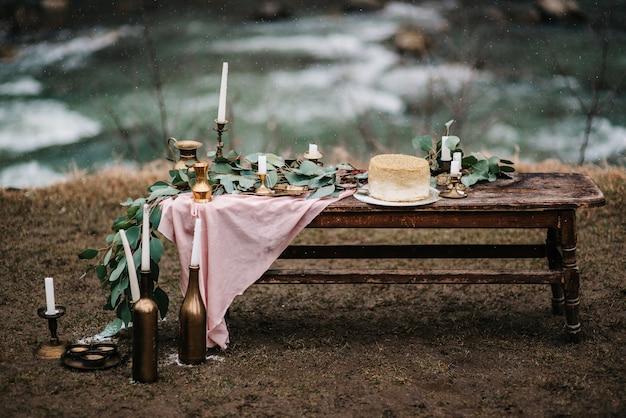 滝の背景に木製のベンチに金色のケーキと結婚式の装飾