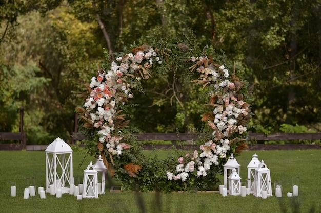 꽃과 양초가 있는 웨딩 장식. 이것은 잎과 꽃의 둥근 아치입니다. 외부 결혼식