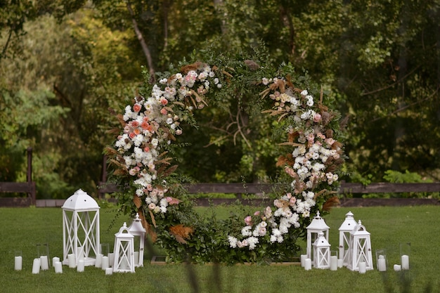 Wedding decor with flowers and candles. this is round arch of foliage and flowers. outside wedding ceremony