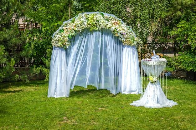 結婚式の装飾結婚式のために用意された白いシフォンで覆われた花のアーチとテーブル