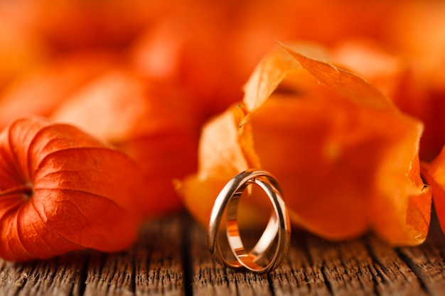 Wedding decoration. red leaves on weathered table with wedding rings
