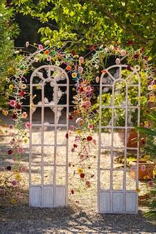 新鮮な花のドアの形でアーチの結婚式の装飾。