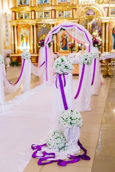 Wedding decorations. the arch is decorated with tulle and violet ribbons with bouquets of roses. ceremony in the church