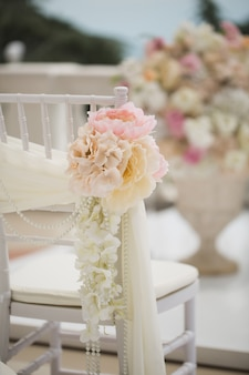 Wedding decorations flowers on chairs. wedding exit registration, white chairs decorated for wedding. wedding setup detail.