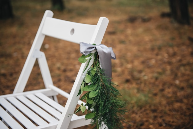 Свадебные украшения цветами на стульях. свадебная выездная регистрация, белые стулья украшены для свадьбы детали свадебной установки.
