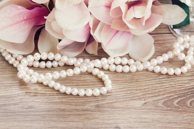 Свадебные украшения - цветы магнолии с нитью жемчуга на деревянном столе
