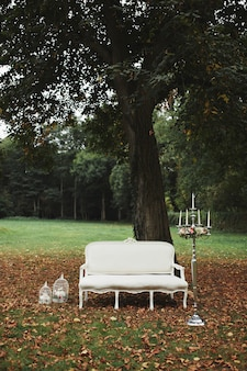 Wedding decorations for photo shoot. classic white sofa in the nature. candlestick in the interior