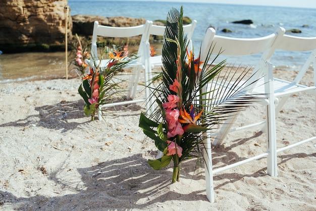 Свадебные украшения в тропическом стиле. установка свадебной церемонии на белом песчаном пляже.