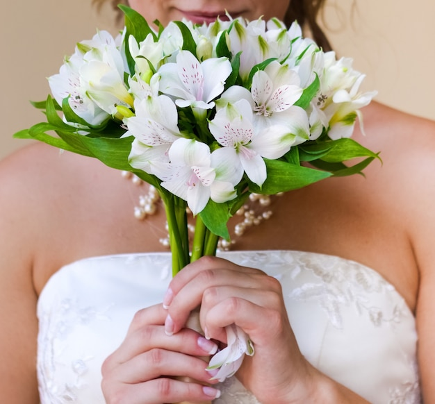 Wedding delicate bouquet of white alstromeria in the hands of the bride close-up
