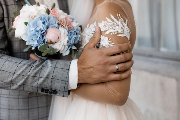 Dettagli del matrimonio, mano di uno sposo con anello nuziale e tenero bouquet da sposa nelle mani della sposa