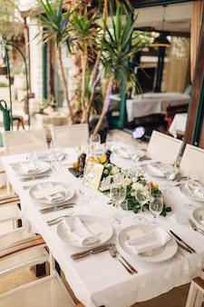 Свадебный обеденный стол фуршет плотная посадка гостей за прямоугольным столом цветочная композиция.