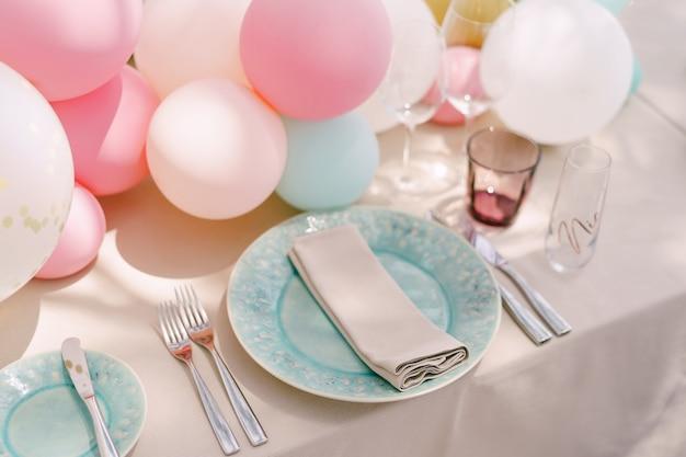 Прием за свадебным обеденным столом. синие тарелки с рисунком и салфеткой, на кремовой скатерти. маленькие воздушные шары на столе. сервировка стола на девичник.