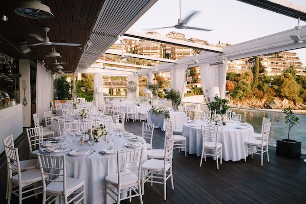 白いテーブルクロスと白いキアヴァリの椅子とラウンドテーブルの結婚式のディナーテーブルレセプション
