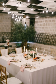 白いテーブルクロスとピンクの6人のための結婚披露宴の長方形のテーブル
