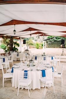 흰색 식탁보와 흰색 치아 바리 의자가있는 결혼식 저녁 식사 테이블 리셉션 라운드 연회 테이블
