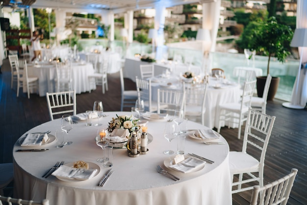 Wedding dinner table reception round banquet table with white tablecloth and white chiavari chairs