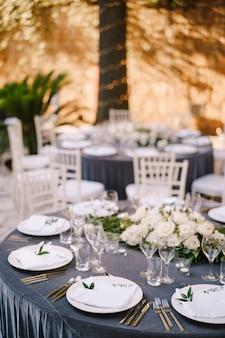 灰色のテーブルクロスの花を持つゲストのための結婚式のディナーテーブルレセプションラウンドバンケットテーブル