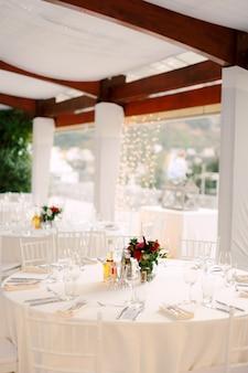 흰색 식탁보와 흰색 chiavary 의자가있는 결혼식 저녁 식사 테이블 리셉션 원형 테이블