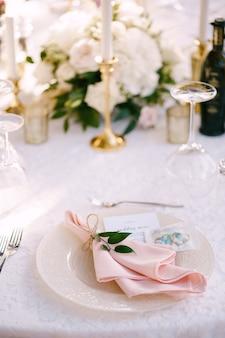 패턴과 헝겊 핑크 냅킨이 있는 분홍색 러너 플레이트가 있는 결혼식 저녁 식탁 리셉션 돌 테이블