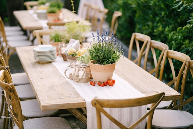 Wedding dinner table reception at sunset outside ancient rectangular wooden tables with rag runner