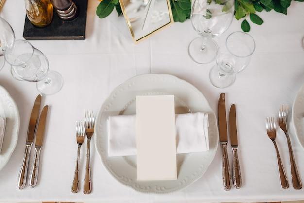 Свадебный обеденный стол прием кремовый лист меню находится в тарелке с тканевой салфеткой столовые приборы.