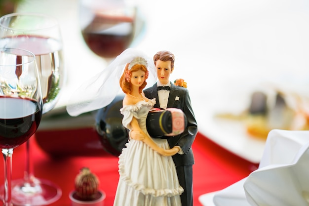 Wedding dolls holding a bottle