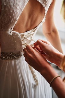 Wedding dress closeup hands knotted corset morning bride