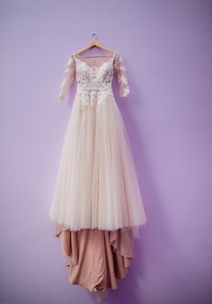 Wedding dress in color of dusty rose hangs on violet wall