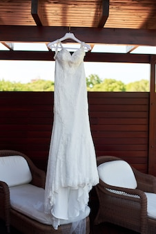 Wedding dress hanging on the ceiling on the balcony