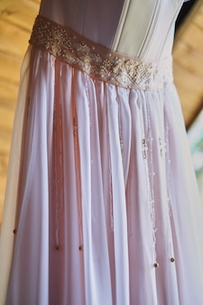 Wedding dress on a hook on a wooden covering