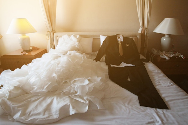Wedding dress and suit lying on the white bed with beautiful sun light in hotel room. valentines day and love for celebration concept.