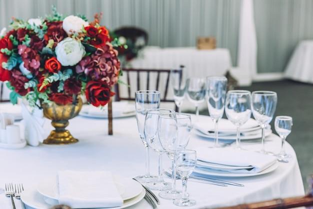 結婚式のエレガントな宴会の装飾と白いテーブルのケータリングサービスによって手配された食品のアイテム