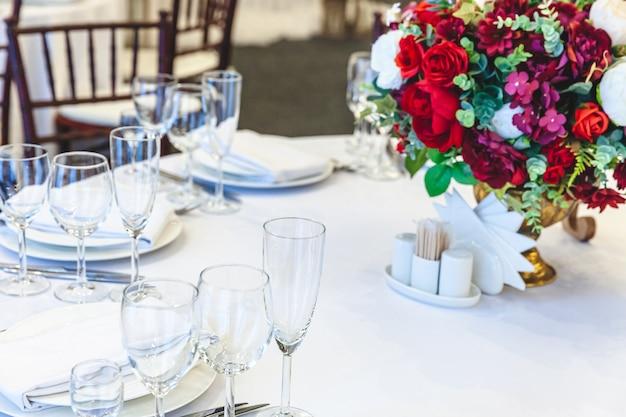 結婚式のエレガントな宴会の装飾と白いテーブルの上の食品のためのアイテム