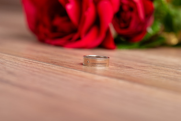 Wedding or engagement ring lying on wooden surface next to beautiful red roses
