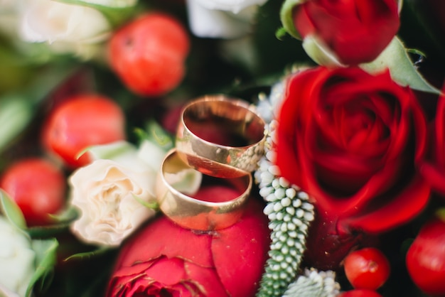 Wedding engagement rings and flowers wedding bouquet background, selective focus, macro